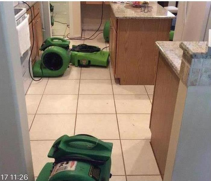SERVPRO equipment used in home to dry kitchen floor with standing water.